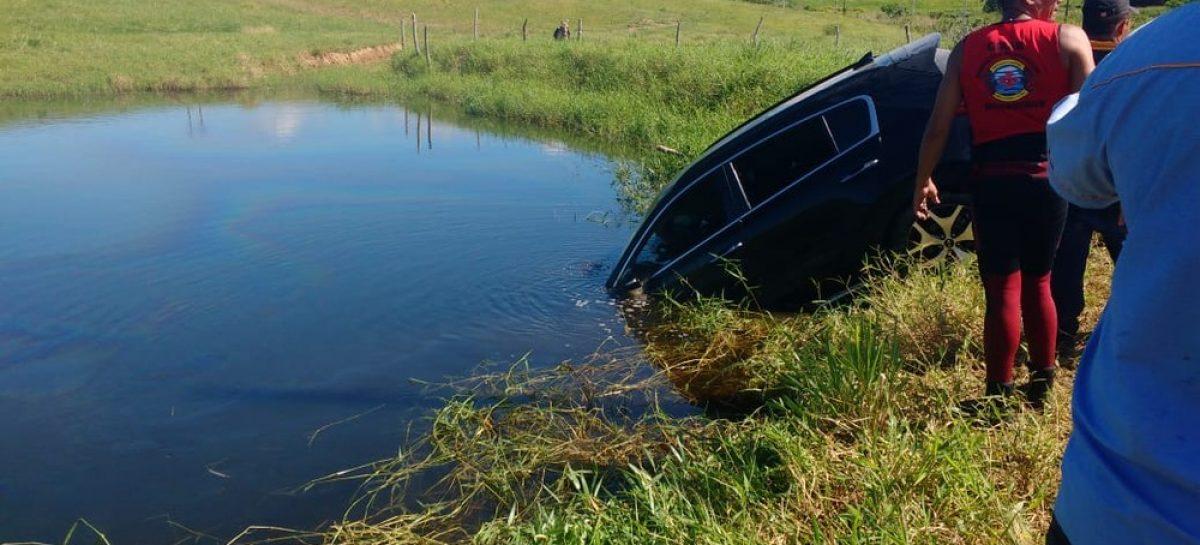 Motorista tenta desviar de veículo na pista e acaba caindo em lago